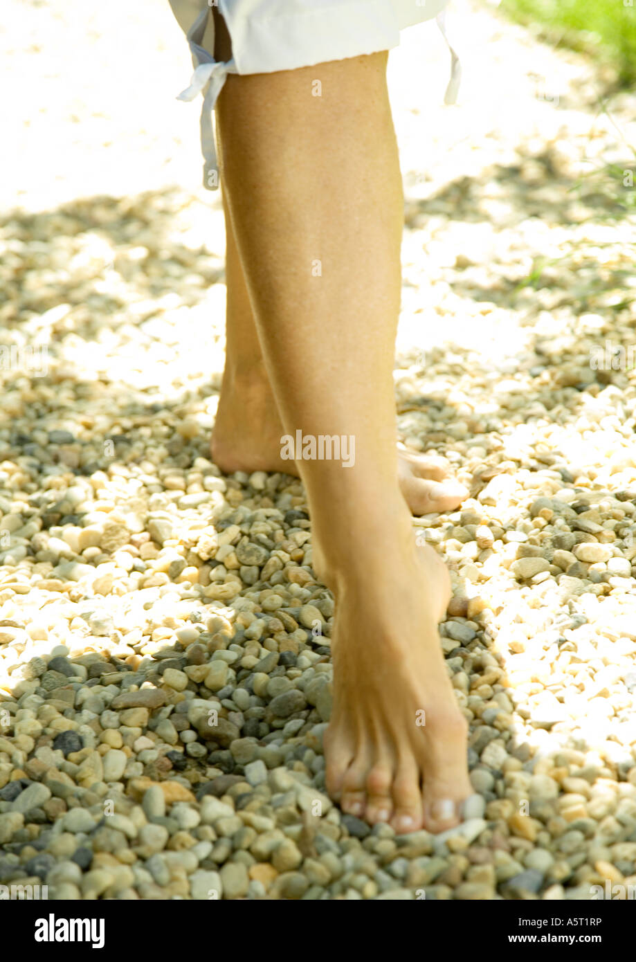 Woman taking step, barefoot on gravel, knee down - Stock Image