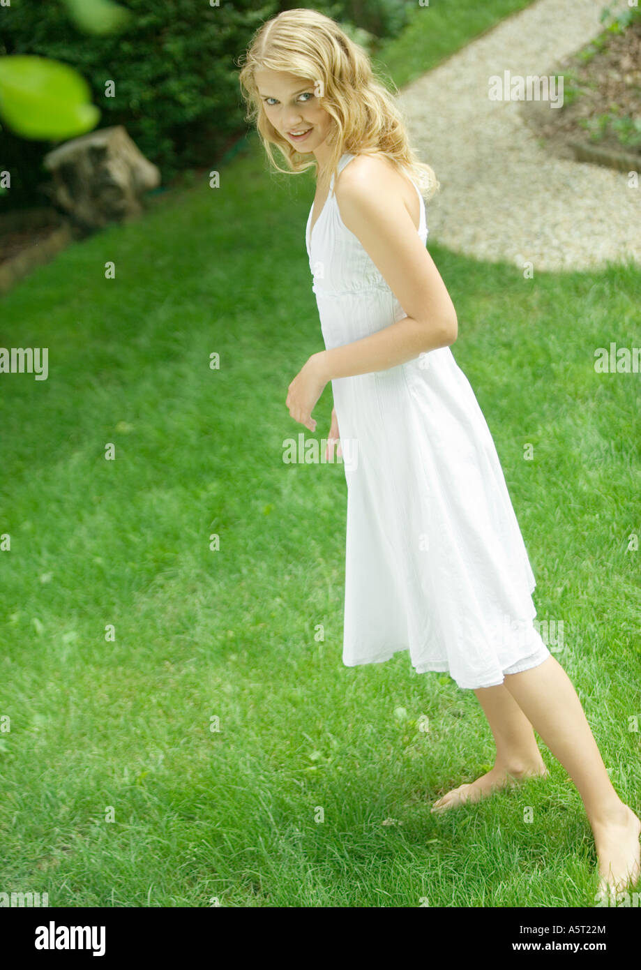 Young woman standing in yard, wearing sundress, smiling at camera - Stock Image
