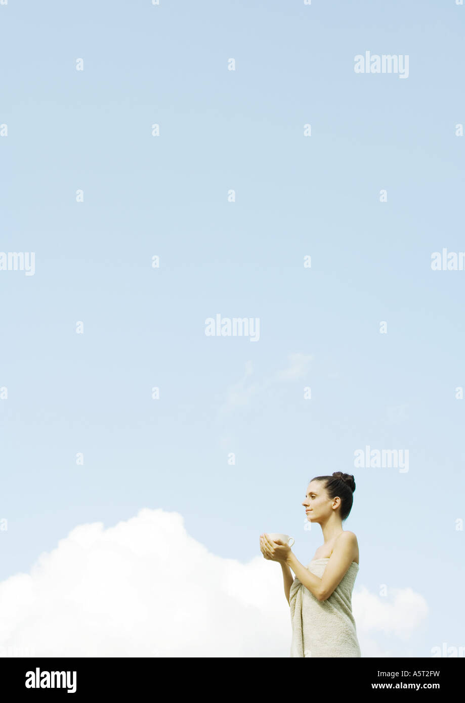 Woman standing wrapped in towel, holding bowl in hands, sky in background - Stock Image