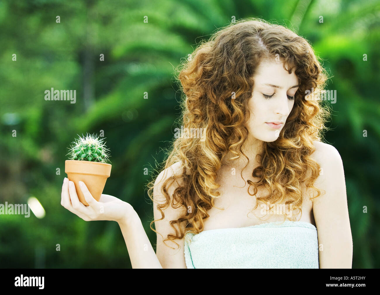 Woman holding cactus in palm, looking away - Stock Image
