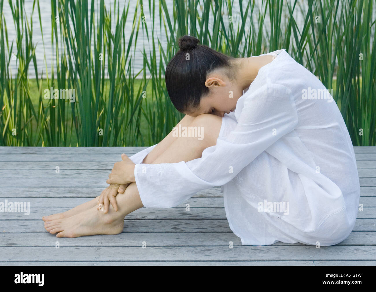 Woman sitting on deck with head on knees - Stock Image
