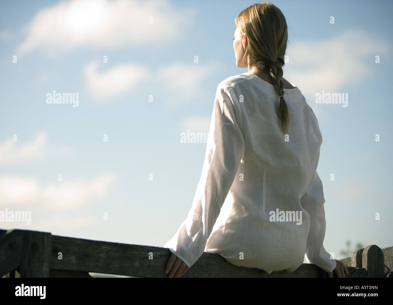Woman sitting on wooden rail, facing sky - Stock Image