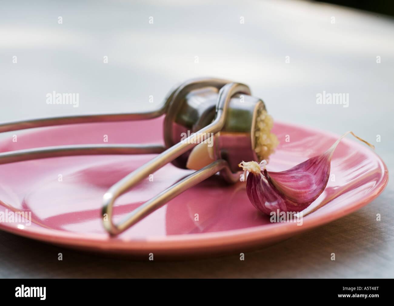 Garlic press and clove of garlic on plate - Stock Image