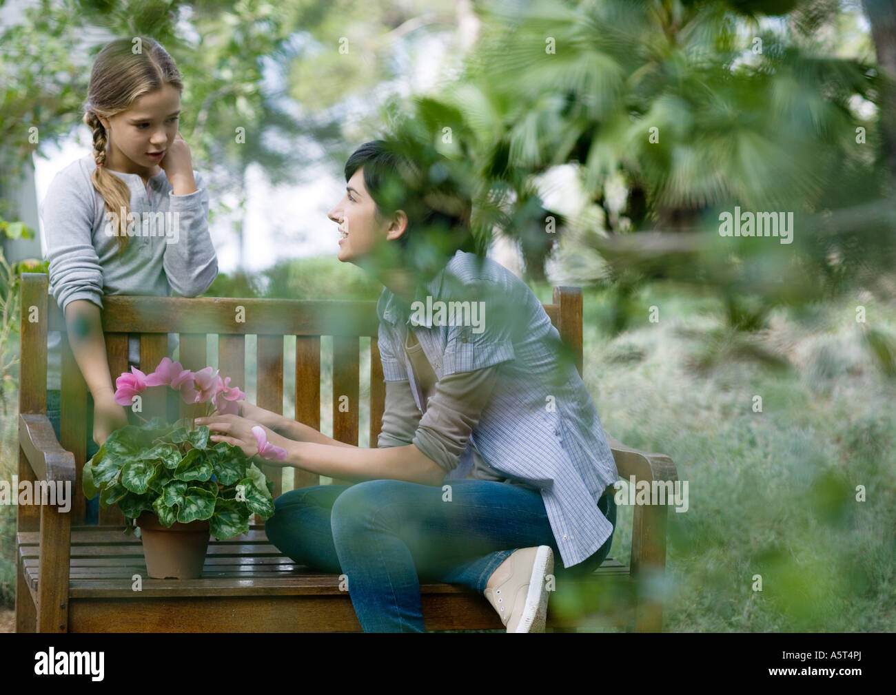 Mother and daughter tending potted plant - Stock Image