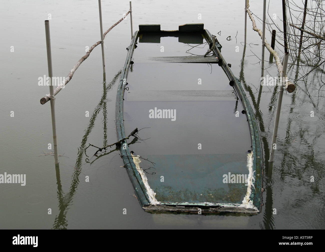 Sunken rowboat in shallow water - Stock Image