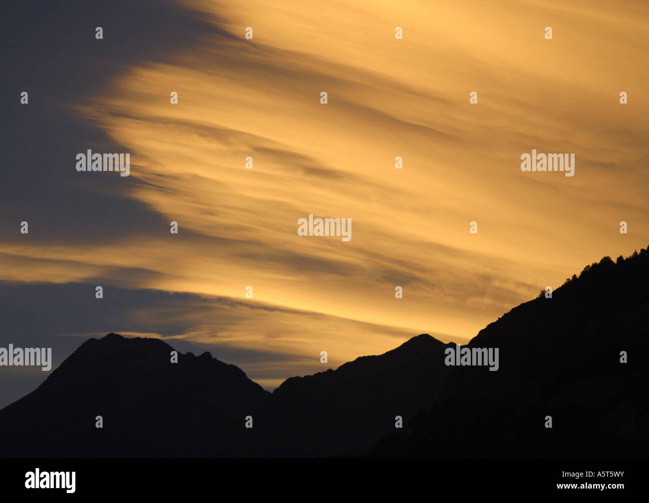 Sky at sunset and silhouette of mountains - Stock Image