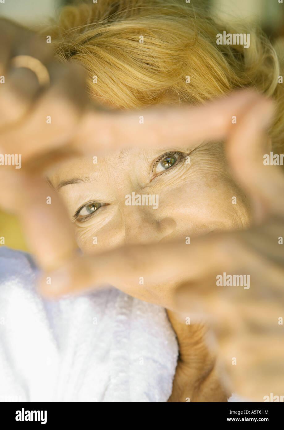 Senior woman looking at camera through finger frame - Stock Image