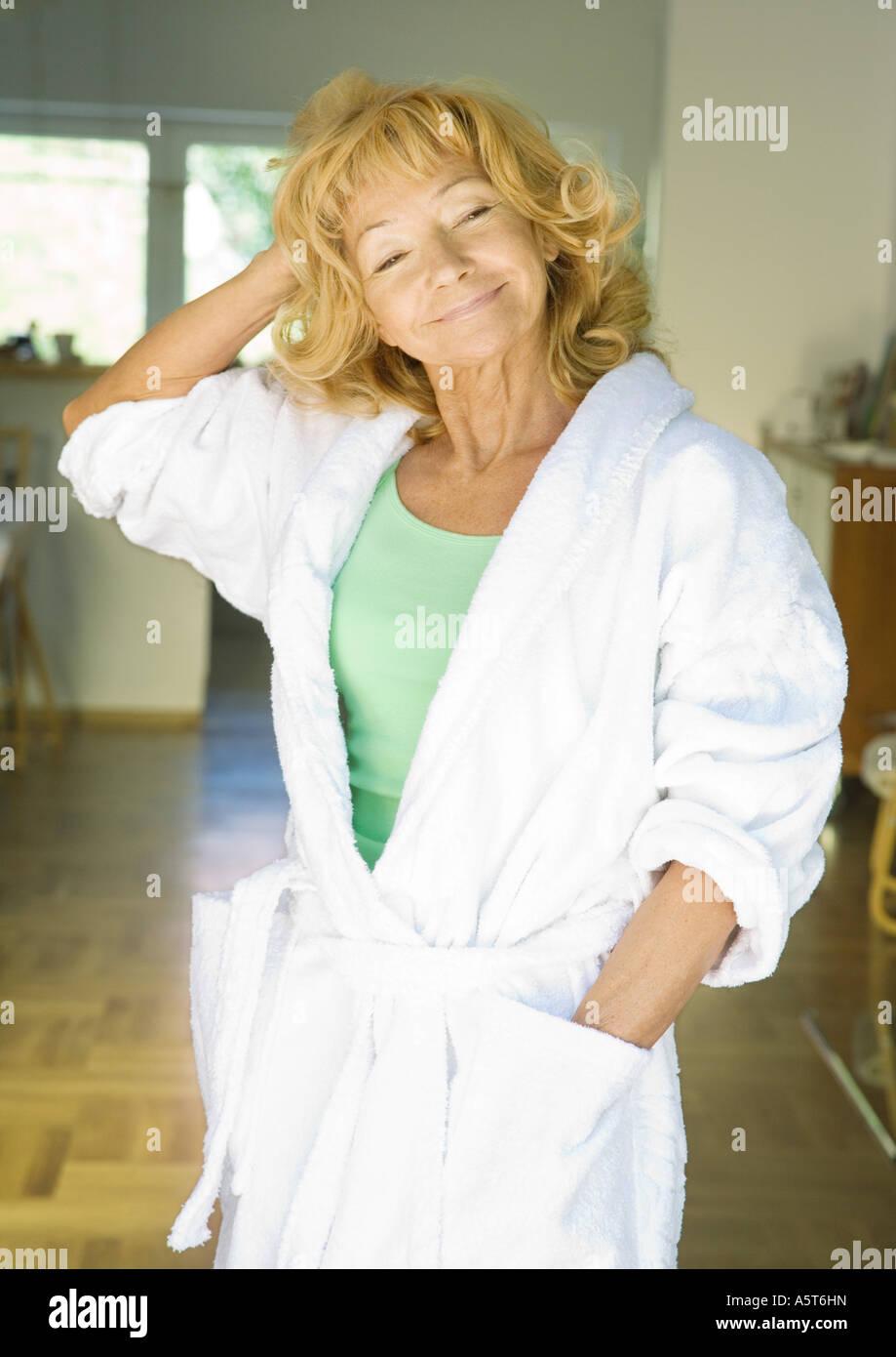 Senior woman standing in bathrobe - Stock Image