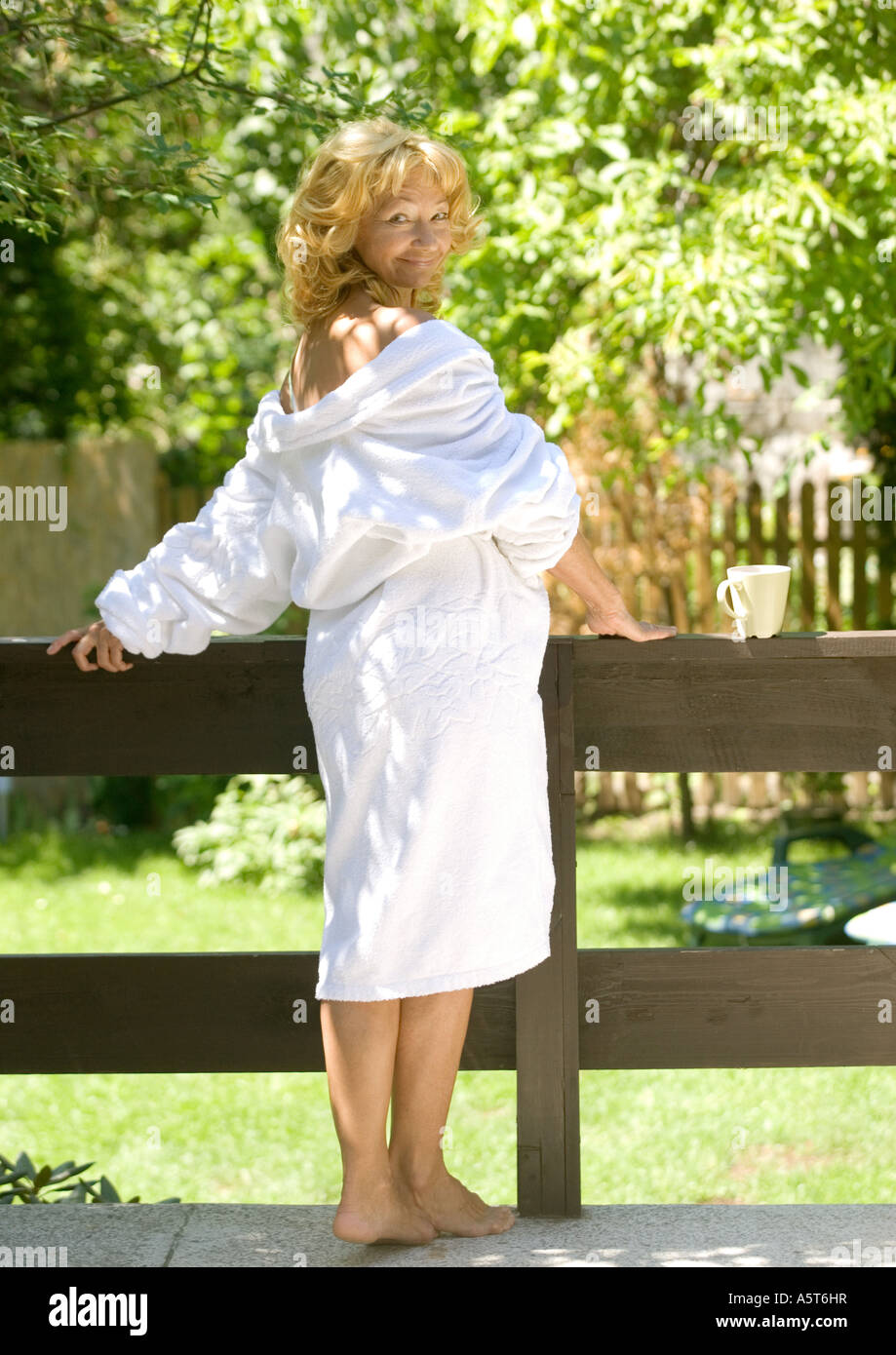 Senior woman in bathrobe, standing outdoors with robe falling off shoulders - Stock Image