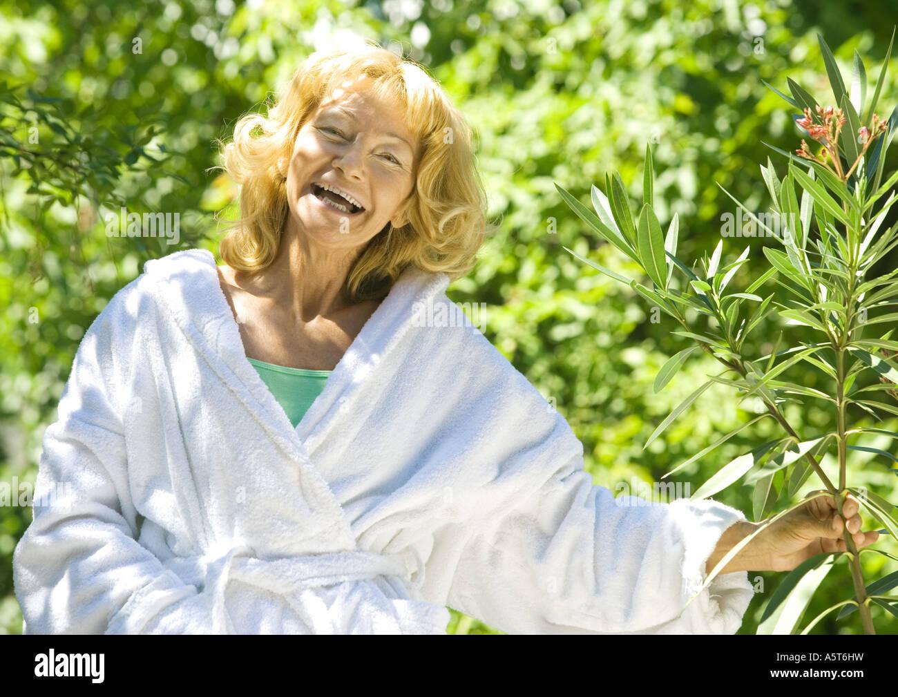 Senior woman in bathrobe holding branch of shrub, laughing - Stock Image