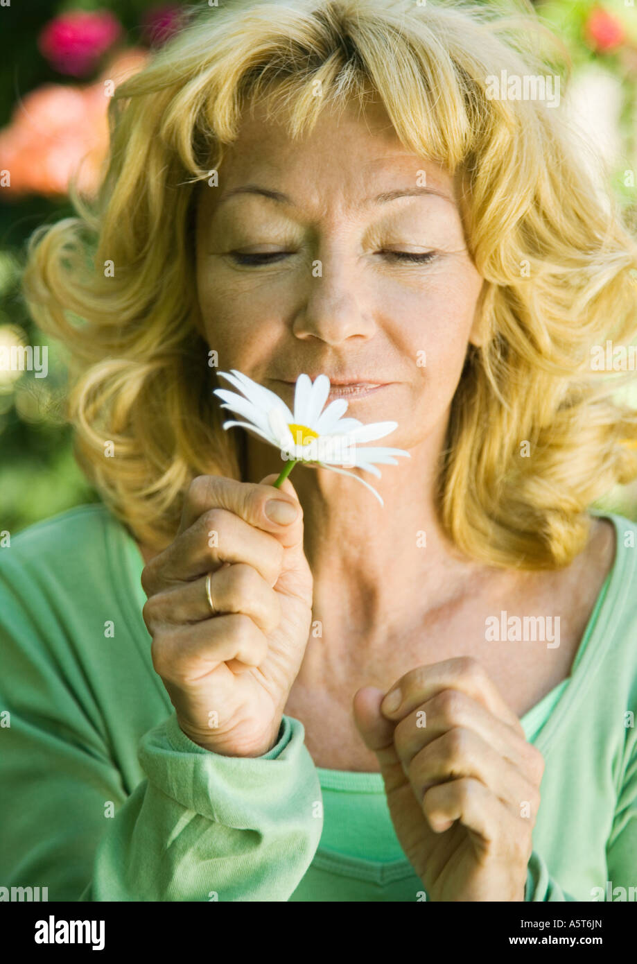 Senior woman smelling daisy - Stock Image