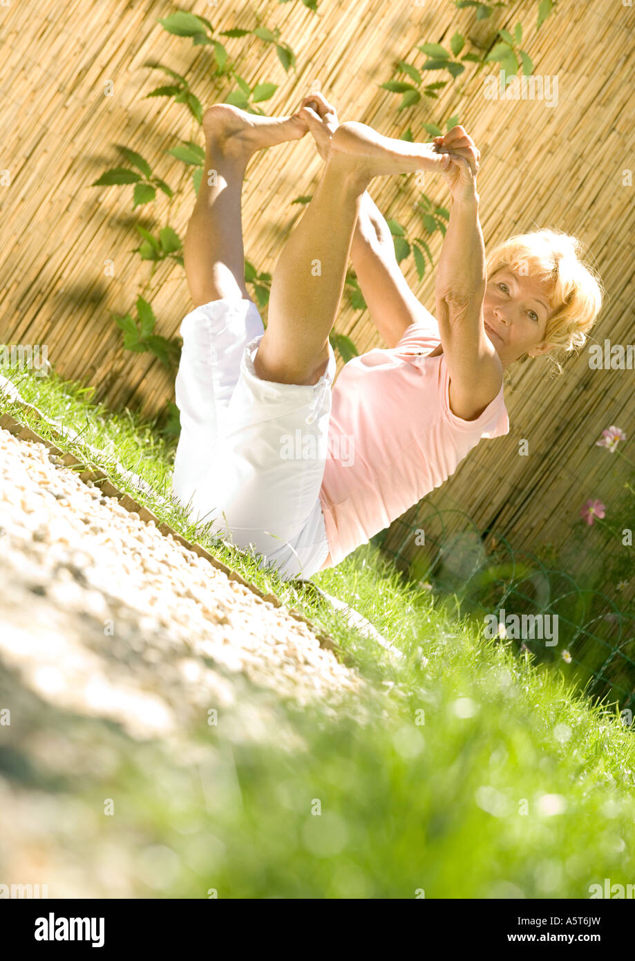 Senior woman stretching outdoors - Stock Image