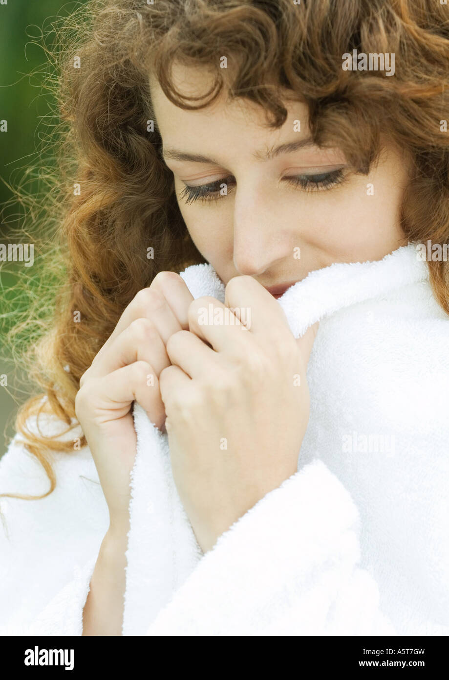 Woman wearing bathrobe, holding up edges of collar - Stock Image