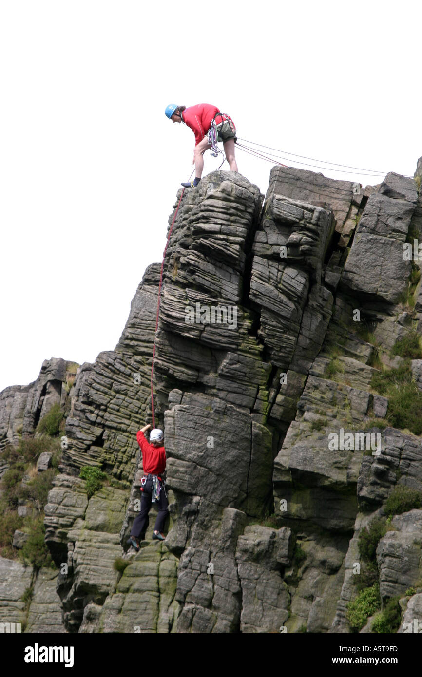 Climbers on Windgather rocks on the Eastern side of the Peak District, Derbyshire, England.  Man at the top of the rocks is belaying a climber on the way up. - Stock Image