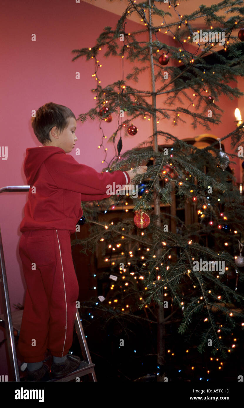 poland boy dressing up christmas tree decoration from a ladder stock image