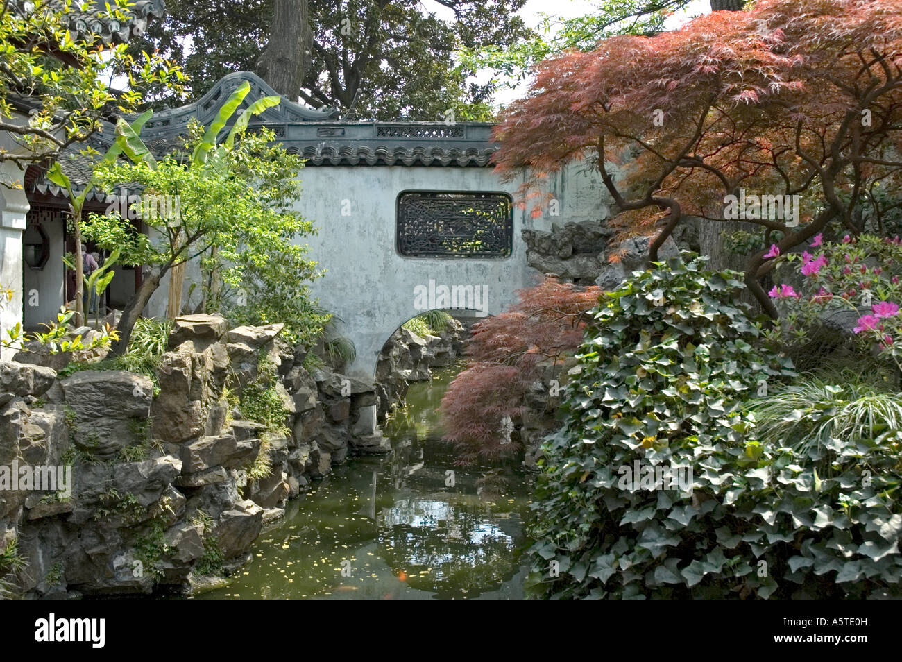 Small Stream bordered by colourful trees and rock formation before passing under a Bridge, Yu Yuan Garden, Shanghai - Stock Image