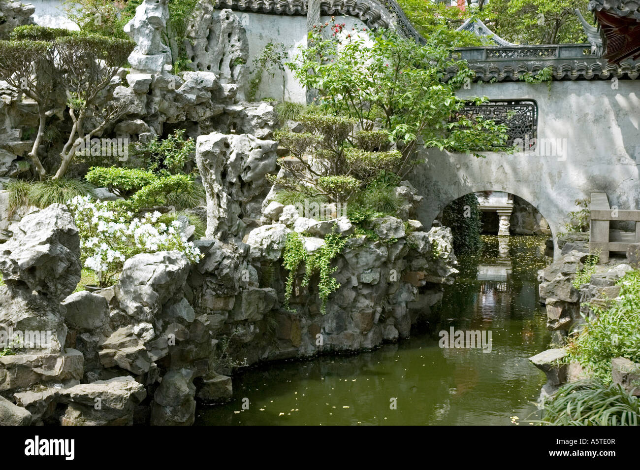 Small Stream flowing between flower embedded rock formation and under a Bridge, Yu Yuan Garden, Shanghai - Stock Image