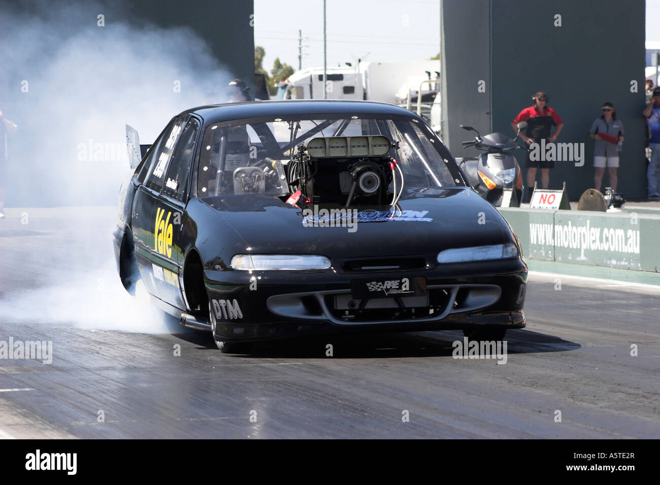 Australian Holden Commodore Supercharged Outlaws drag car performing smoky burnout on quarter mile race track Stock Photo
