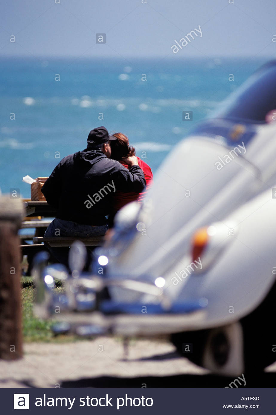Senior couple watching the view, with their classic VW Beetle in the foreground. - Stock Image