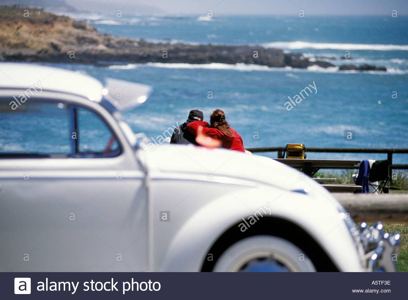 A classic VW Beetle and a couple watching the ocean view. - Stock Image