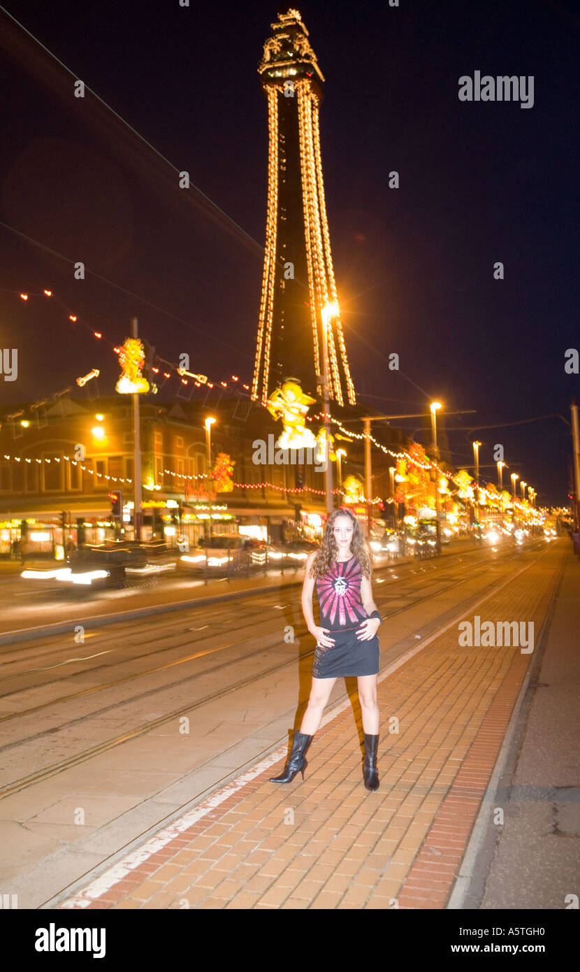 Pretty girl in front of an illuminated Blackpool tower during the annual illumunations,Lancashire,England Stock Photo