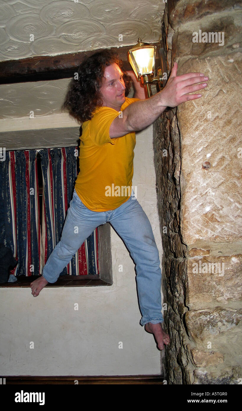 Young men indoor climbing the walls in an Inn after a few beers during a stag party weekend Stock Photo