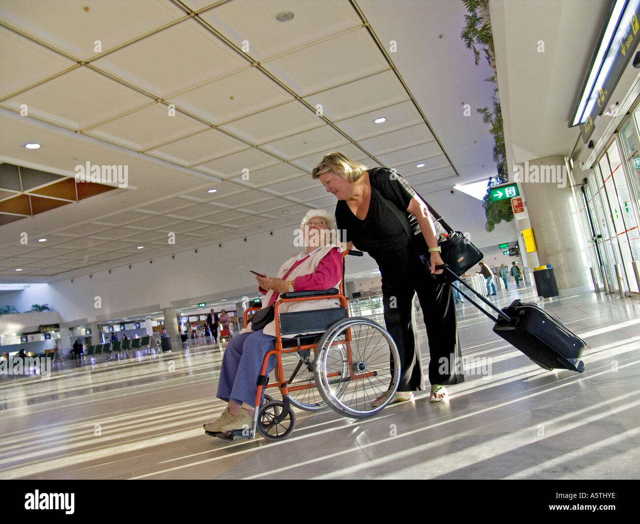 Elderly Woman In Wheelchair With Female Carer Companion On Airport Concourse Preparing To Travel Stock Photo Alamy