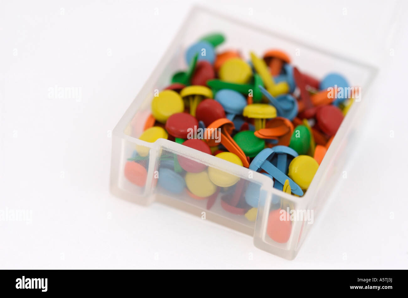 Container full of coloured brads (paper fasteners) used in papercrafts. - Stock Image