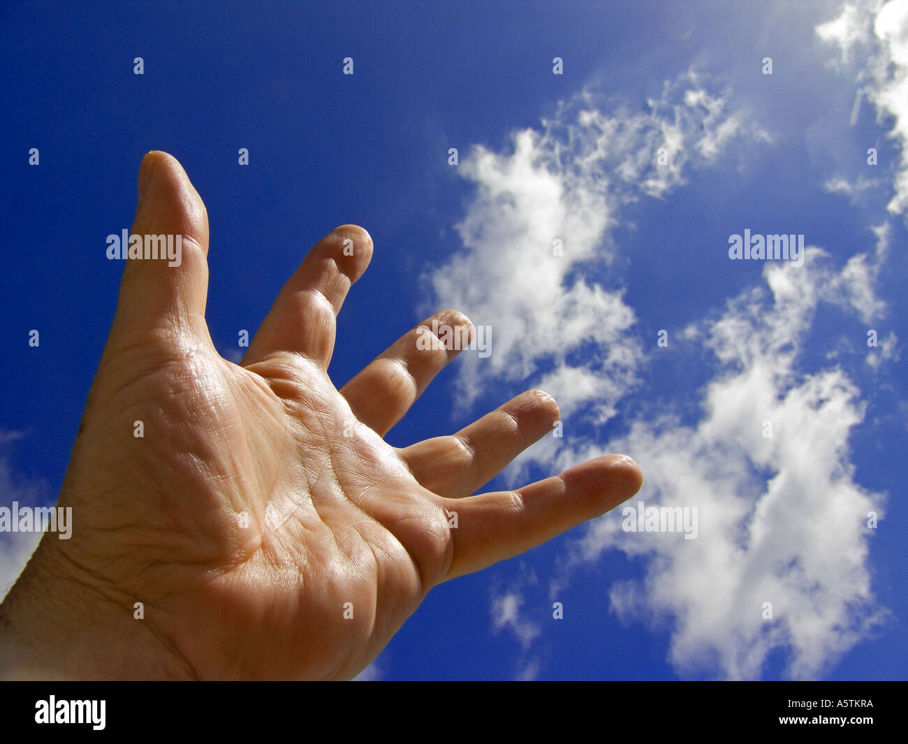 Male hand stretching up to a blue sky with clouds - Stock Image