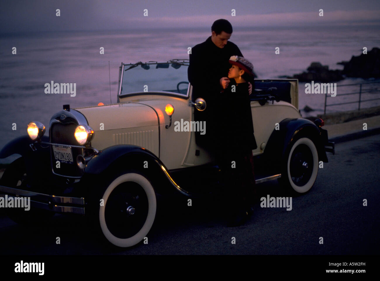 Painet hl1090 couple embracing next antique car california monterey man male woman female old automobile beach front - Stock Image