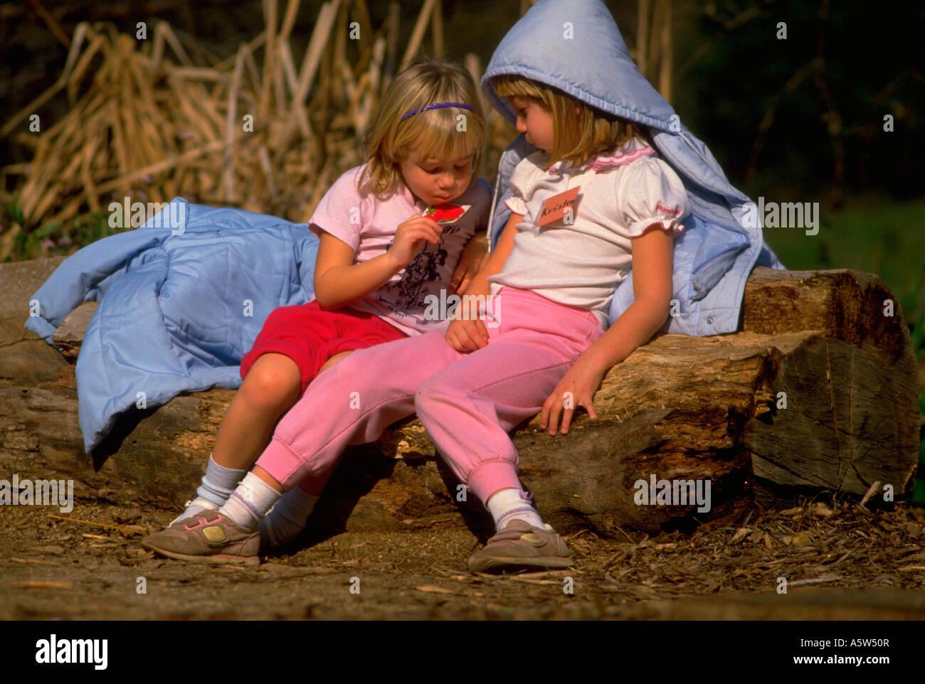 Painet hl0957 two girls children kids girl log sitting fascination exploring woods nature california focused youth - Stock Image