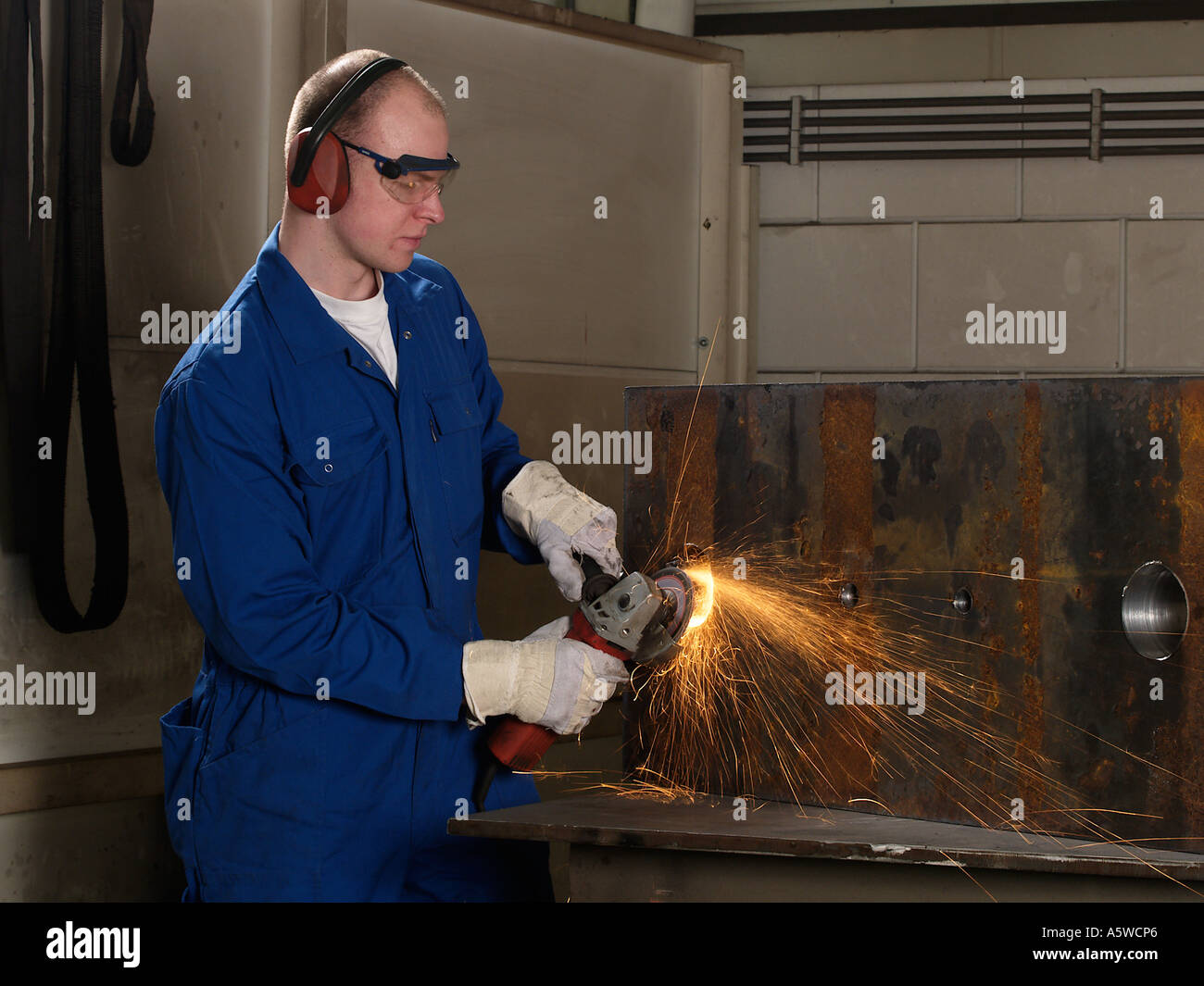 Man wearing protective gloves goggles and ear protectors using angle grinder on iron block sparks heat friction - Stock Image