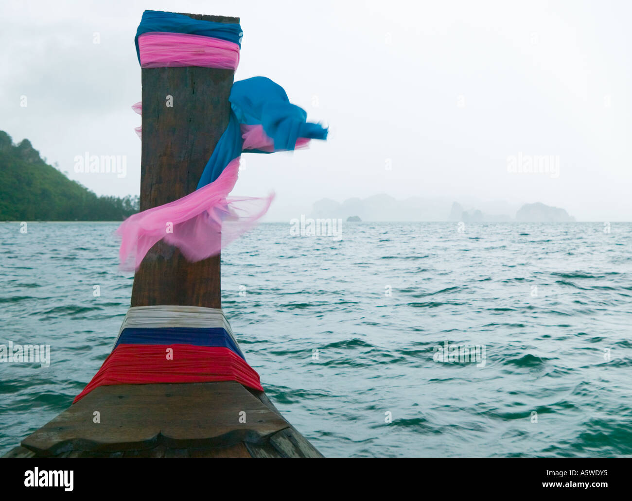 Bow of a long tail boat heading toward land on a rainy windy day in Southern Thailand during monsoon season - Stock Image