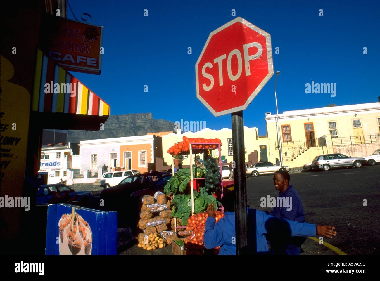 Painet hk2749 south africans relaxing by stop sign malay quarter capetown relax neighborhood fruitstand community Stock Photo
