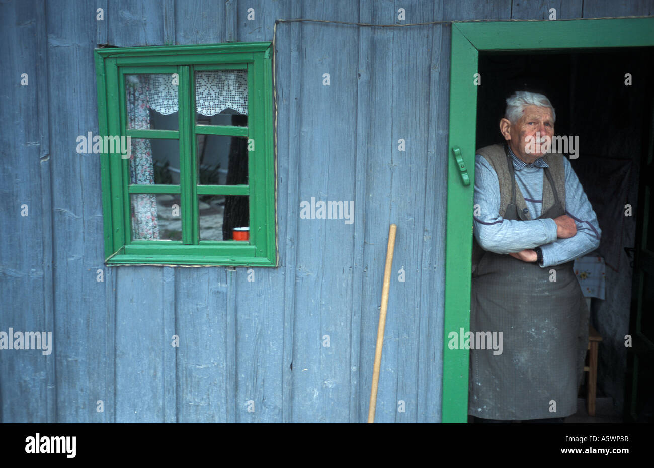 Man in the doorway of his house in the village of Corund in the Hungarian Szekely region of Transylvania Romania Stock Photo