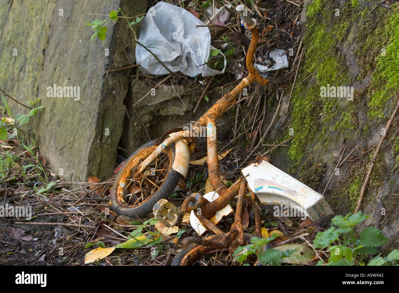 Rusty bicycle and plastic bag thrown away on canal towpath - Stock Image