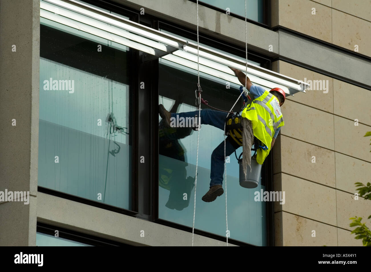 Window cleaner using industrial rope access techniques at work on a hotel building, Manchester, UK - Stock Image