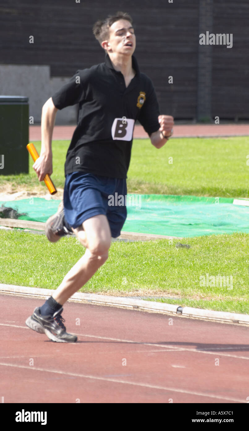 Young man on running track in relay wearing different coloured tops athletics competition - Stock Image