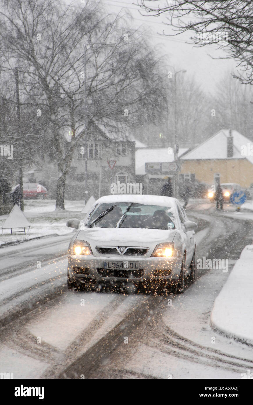 Car driving slowly to work on a snowy winters morning England - Stock Image