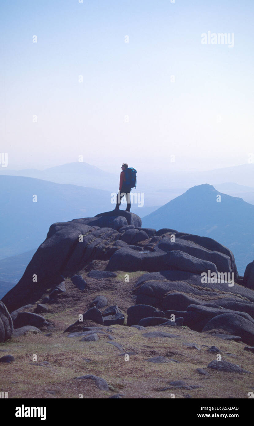 Walker silhouetted on the summit of Slieve Bearnagh, Mourne Mountains, Co Down, Northern Ireland - Stock Image