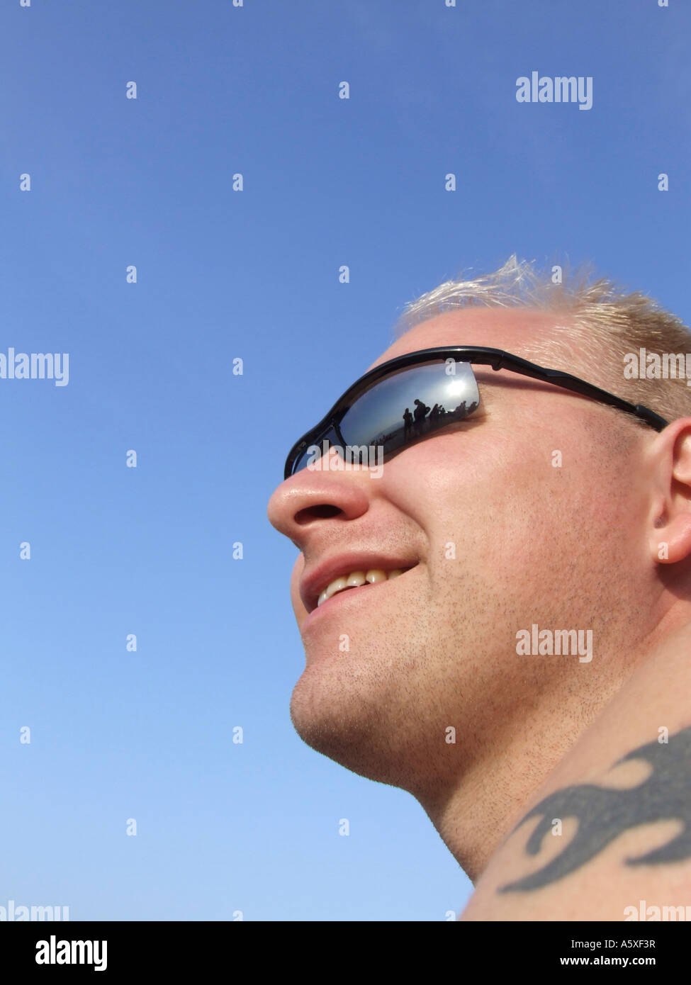 f57e2ea3dc22 Mid adult man wearing sunglasses close up low angle view - Stock Image
