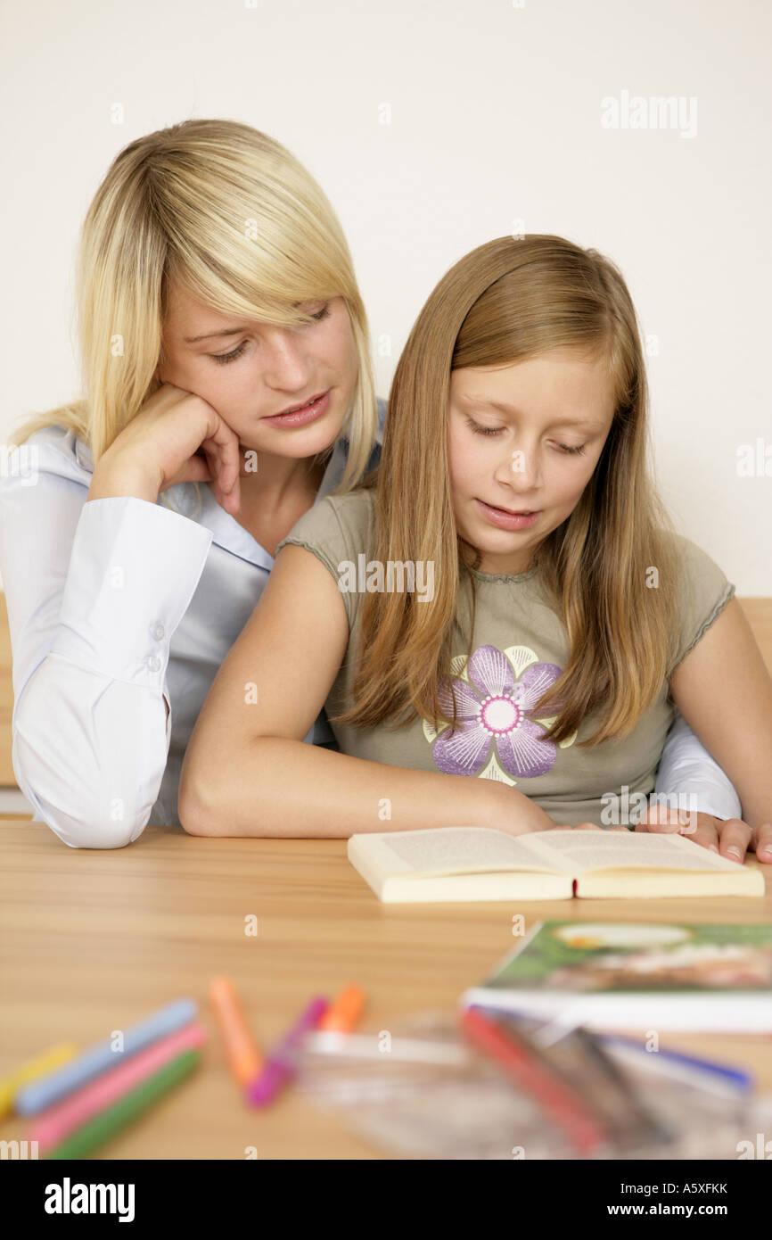Mother taking homework of daughter Stock Photo