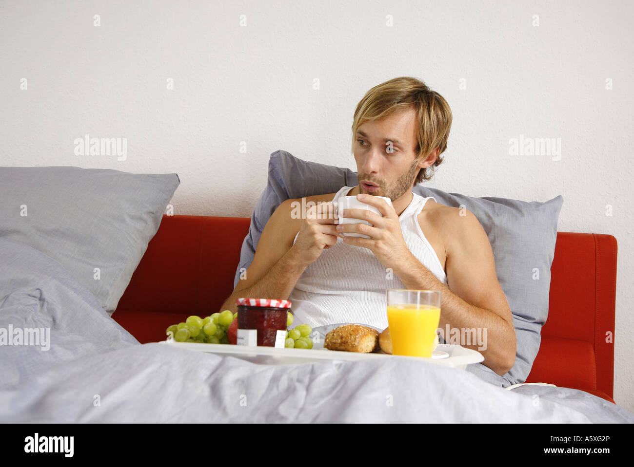Young man having breakfast on bed portrait Stock Photo