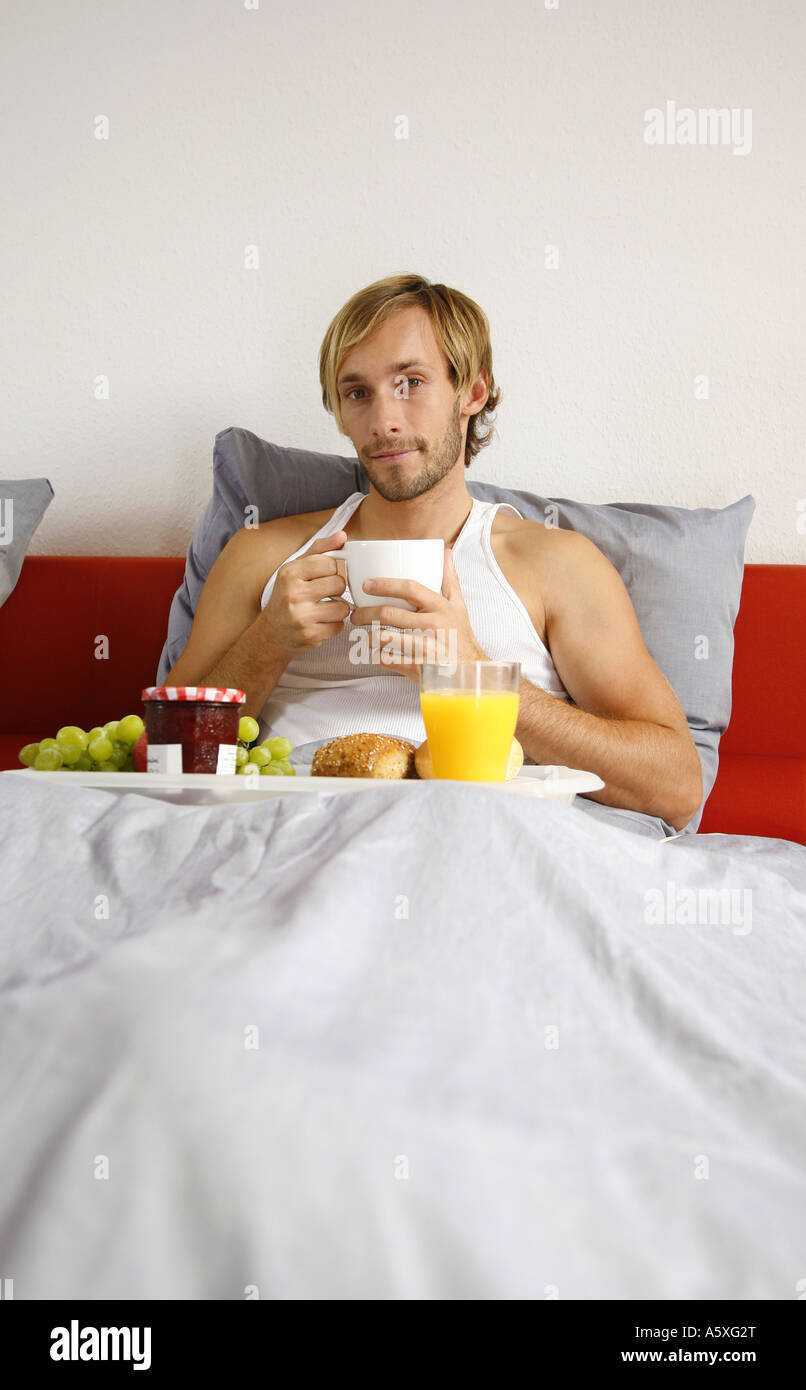 Young man having breakfast on bed smiling portrait Stock Photo