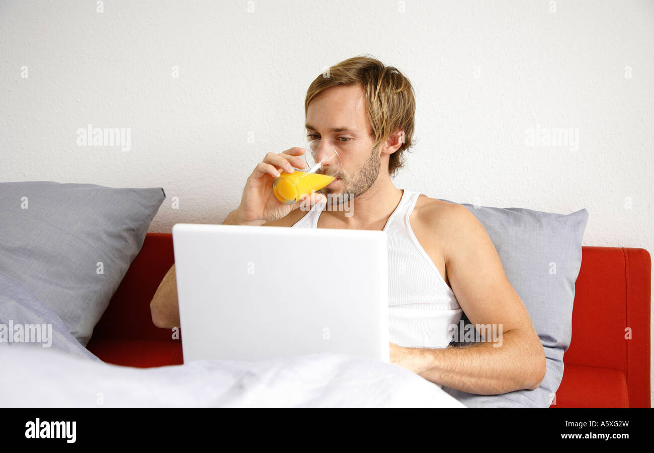 Young man using laptop on bed drinking juice Stock Photo