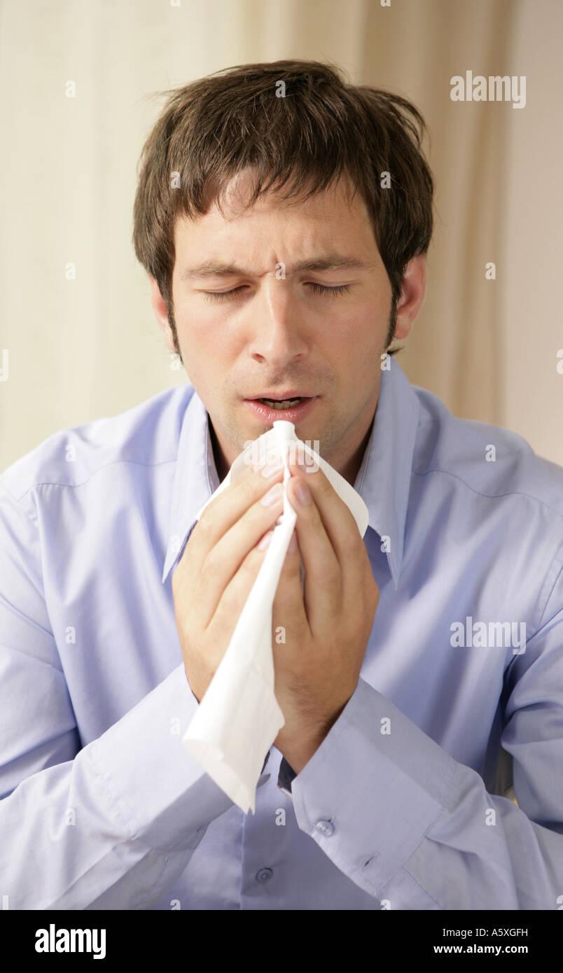 Young man sneezing close up Stock Photo