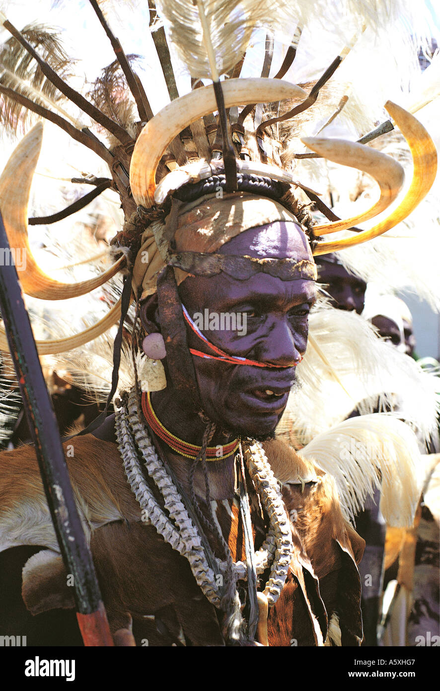 Luo warrior elder with spectacular traditional dress and headdress of ostrich feathers and hippo tusks Kisumu Kenya East Africa - Stock Image