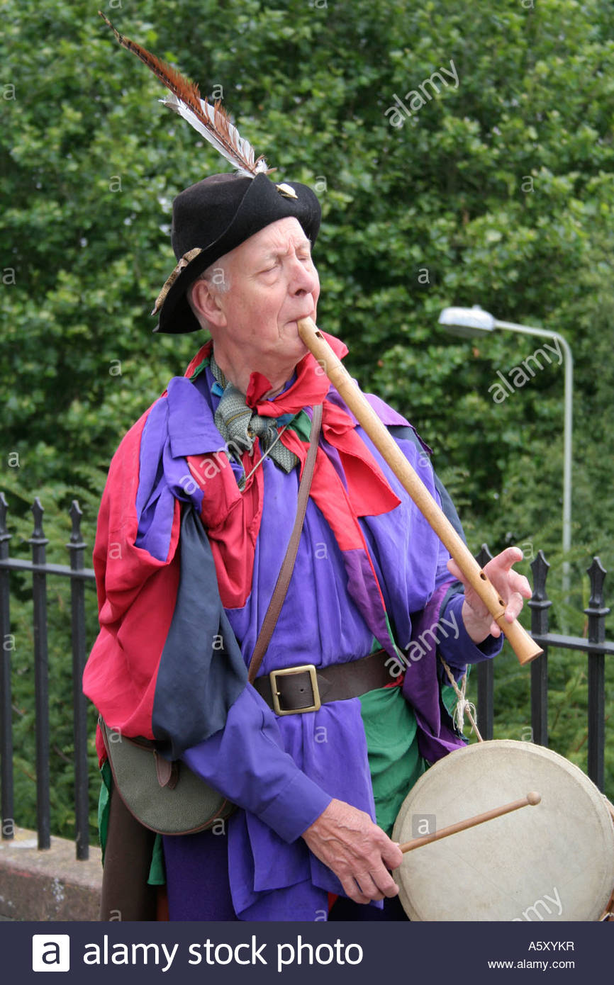 medieval street musician playing a wooden flute and drum - Stock Image