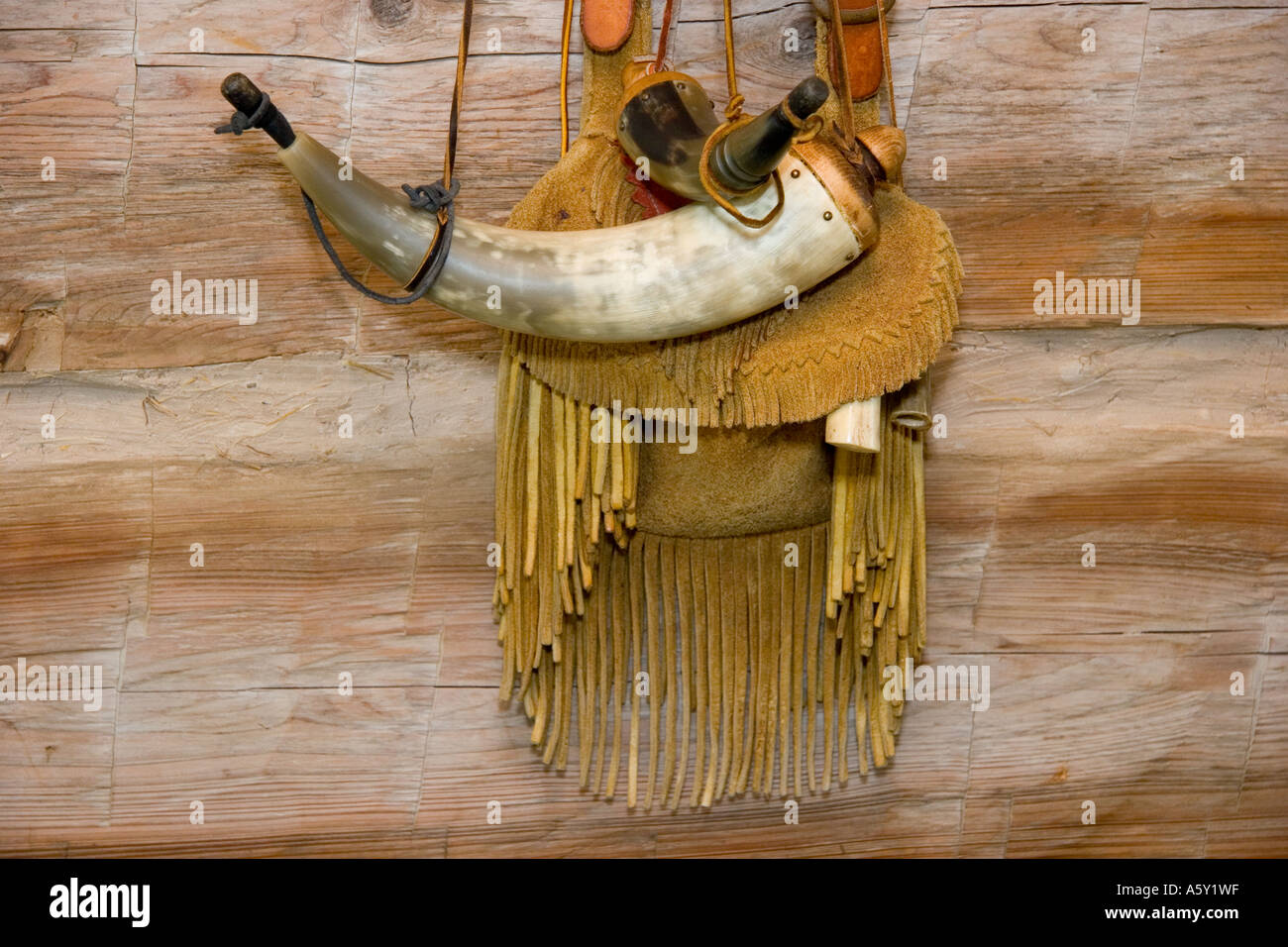 Antique Gun Supplies, Leather Pouch with Fringe, Gunpowder Horn Hanging on Cabin Wall - Stock Image