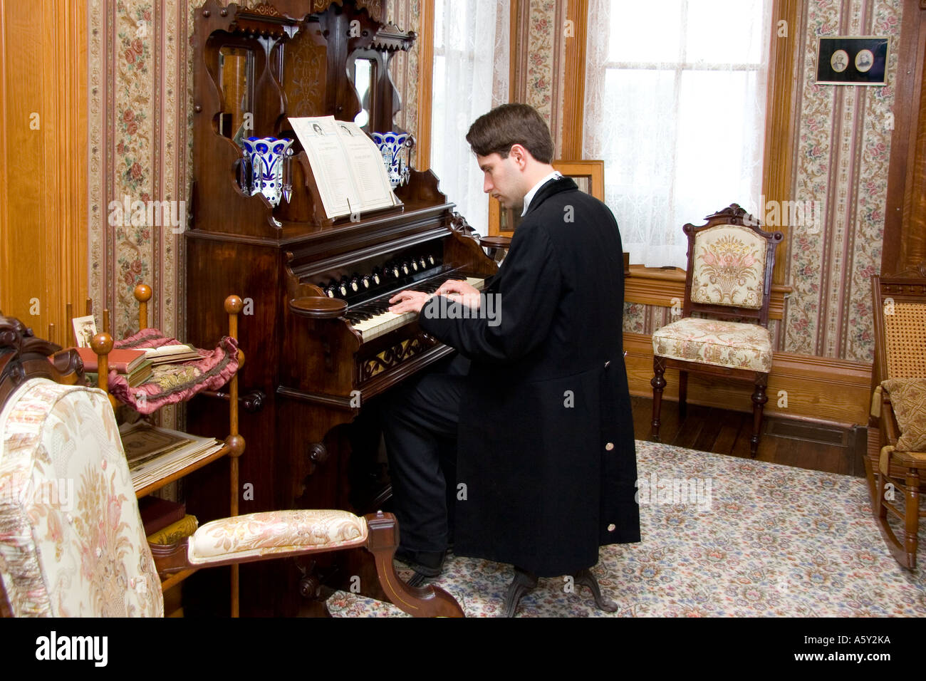 Male Dressed in Victorian Clothing Playing Victorian Pump Organ in Parlor, Nineteenth Century Texas Country Home - Stock Image